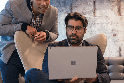 תמונה של שני אנשים מביטים במחשב נישא