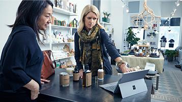 שתי נשים מביטות במחשב בחנות