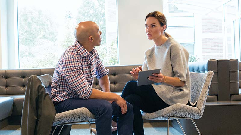 Egy férfi és egy nő beszélget egy irodában