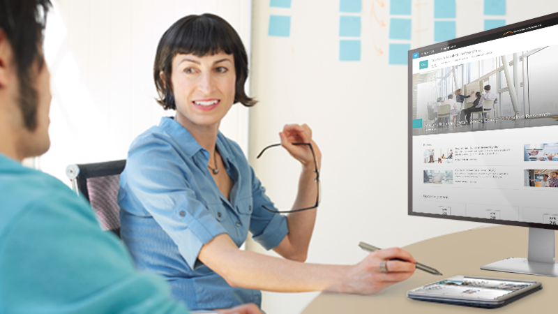 Csapattagok egy kommunikációs SharePoint-webhelyet megjelenítő táblagéppel és asztali géppel