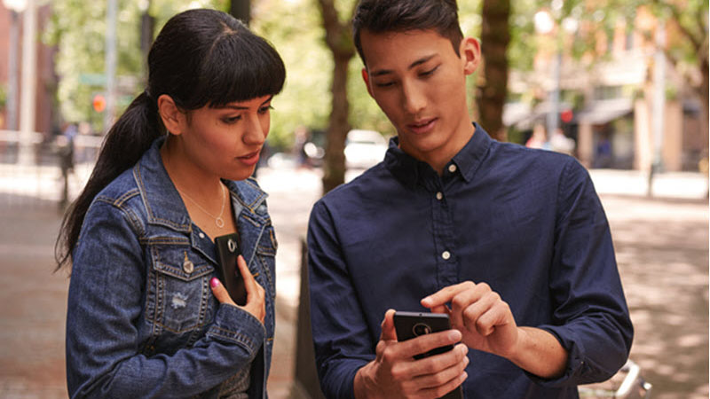 Dua pekerja di luar menggunakan smartphone