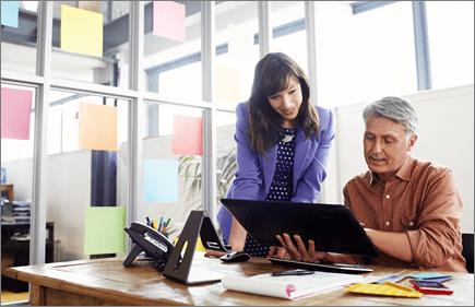Foto dua orang bekerja menggunakan komputer tablet.