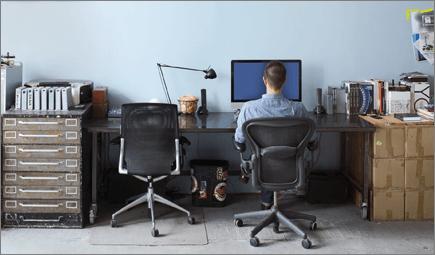 Foto seorang pria duduk di meja, bekerja dengan komputer.