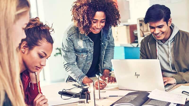 Empat mahasiswa atau siswa SMA mengerjakan tugas bersama-sama dengan laptop dan buku