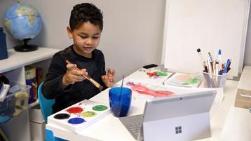 Seorang anak laki-laki menggunakan cat di atas kertas sambil melihat laptop Surface yang terbuka