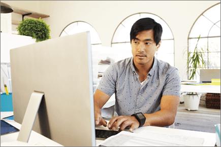 Foto seorang pria yang sedang bekerja di depan komputer