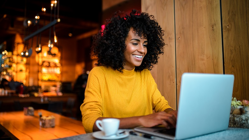 foto seorang wanita di sebuah kafe dengan laptopnya