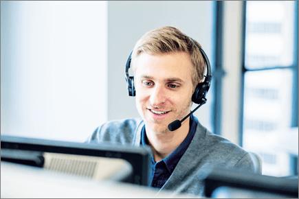 Foto seorang pria yang melihat komputer dan memakai headset.