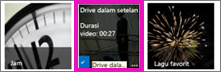 Cuplikan layar pustaka video. Dua dari video di pustaka mempunyai gambar mini konten video, dan salah satu gambar hanya memperlihatkan grafis yang mewakili strip film.