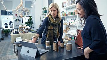 Dua perempuan menatap komputer di sebuah toko