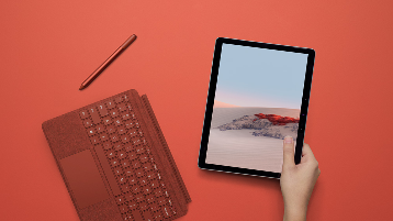 Immagine di una mano che tiene Surface Go 2 con la cover con tasti Poppy Red e la penna per Surface staccata