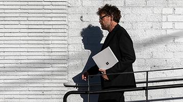 Un uomo che cammina con un Surface Book in mano