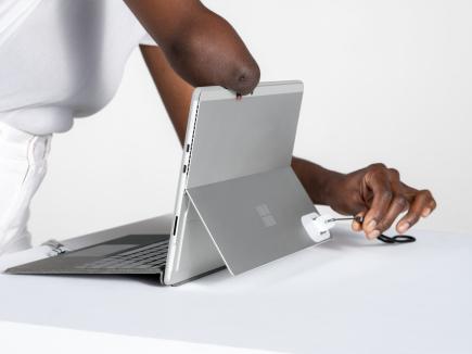 ネック ストラップが付いたアダプティブ キット のオープナーを使用して、Surface Pro キックスタンドを開く女性。