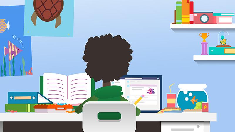 机の前に座っている生徒