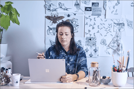 ノート PC で作業している女性の写真