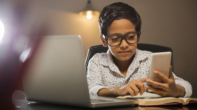 ノート PCでクイズを解いている若い学生の写真。