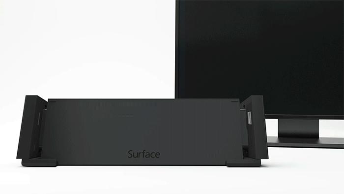 アニメーション画像は、下にスライドされてドッキング ステーション差し込まれる Surface デバイスと、その背後でオンになって Surface と同じ画像を表示するモニターを示しています