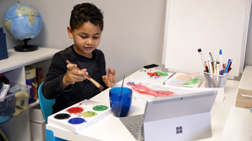 開いた Surface Laptop を見ながら、紙に絵を描く少年。
