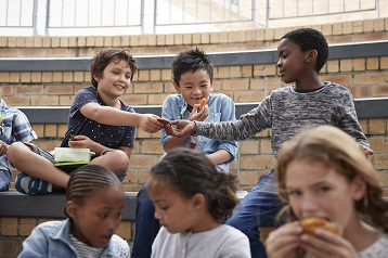 お菓子や健康的なスナックを食べている子供の写真