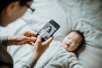 赤ちゃんの携帯電話の写真を撮っているお母さん