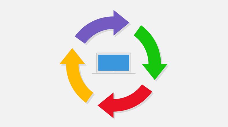 Kompiuterio simbolis su spalvotomis apvaliomis rodyklėmis aplink jį