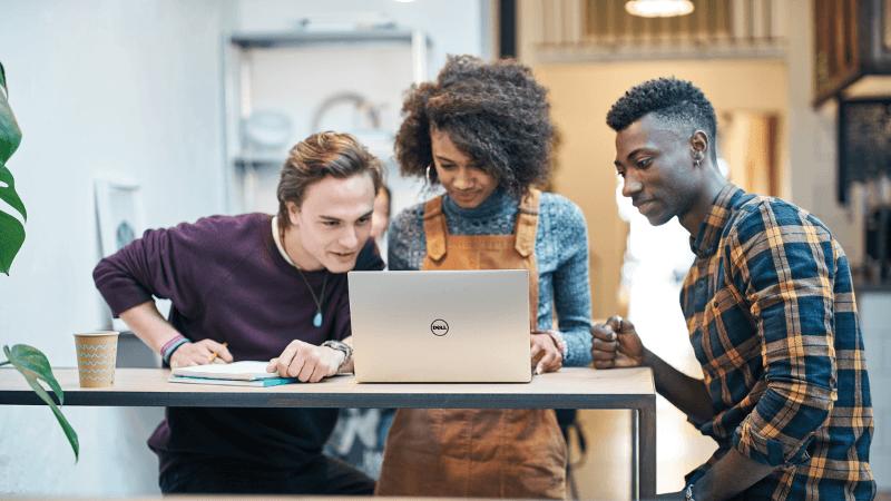 Trys jauni žmonės žiūri į nešiojamojo kompiuterio ekraną