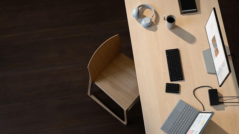 """""""Surface Pro"""", """"Surface Headphones"""", pelė ir klaviatūra ant rašomojo stalo"""