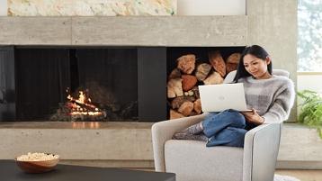 Moteris, sėdinti ir dirbanti nešiojamuoju kompiuteriu
