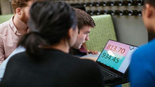 Grupė žmonių, žiūrinti į padidintą kompiuterio ekraną