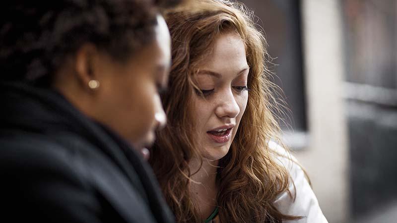 Divas sievietes runā un skatās uz kādu projektu
