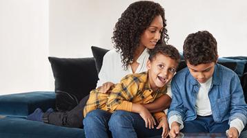 Māte ar diviem dēliem kopā skatās planšetdatorā