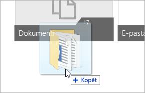 Ekrānuzņēmums, kurā redzams kursors, kas velk mapi uz OneDrive.com