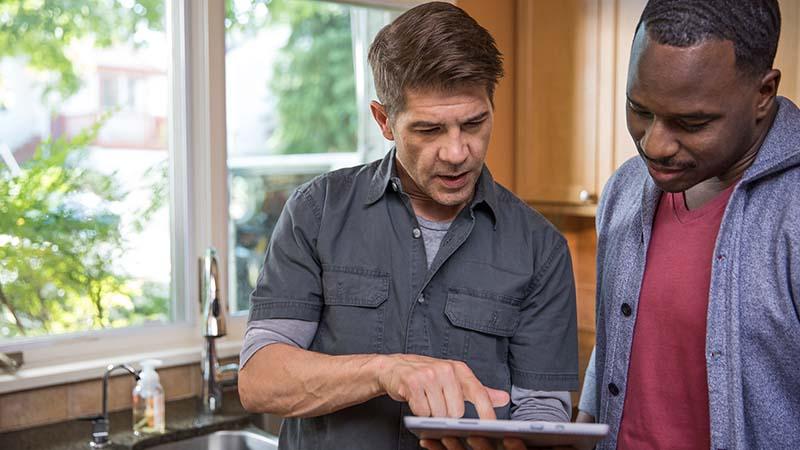 Divi vīrieši virtuvē, kas skatās uz planšetdatoru