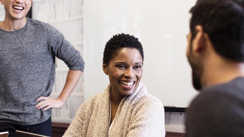 Sieviete un divi vīrieši smaida un sarunājas birojā