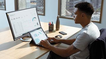 Vīrietis izmanto Surface ierīci ar ārējo monitoru