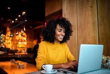 Smaidoša jauna sieviete ar klēpjdatoru kafejnīcā