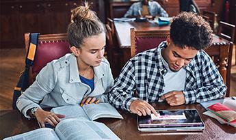 Divi studenti mācās bibliotēkā