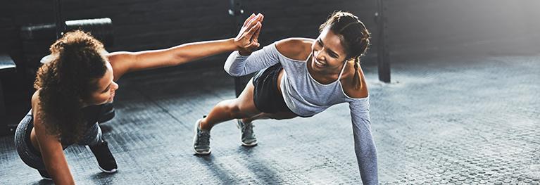 Attēls, kurā redzamas divas kopīgi sportojošas sievietes