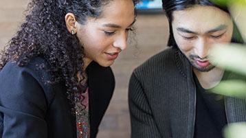 Fotoattēls ar diviem cilvēkiem, kuri kopīgi strādā birojā