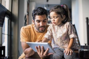 Tēvs un jaunākā meita skatās planšetdatorā