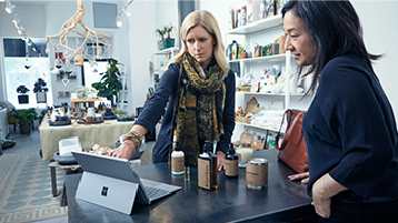 Divas sievietes skatās datorā veikalā
