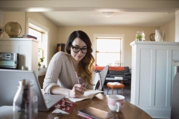 Sieviete raksta dienasgrāmatā pie pusdienu galda