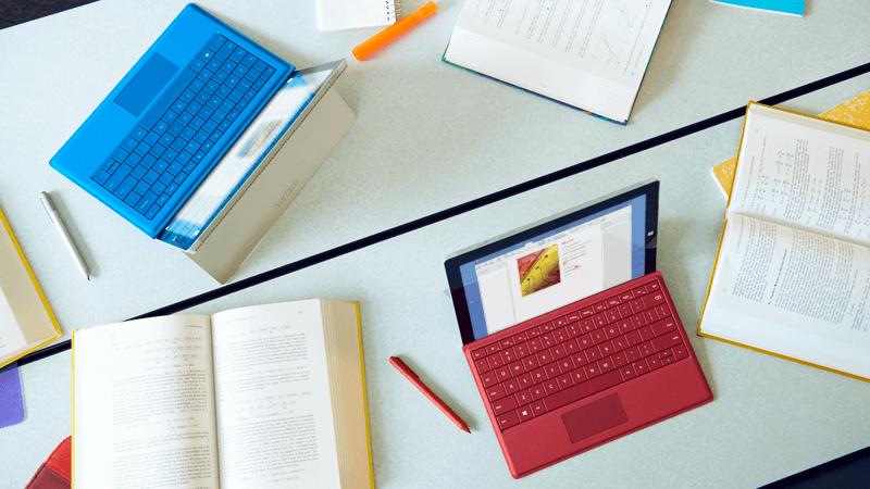 Foto dua komputer riba, setiap satu terbuka dan bekerja pada dokumen Word yang sama.