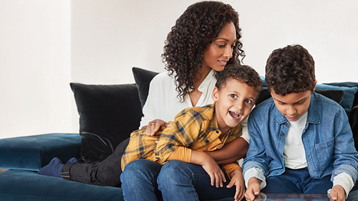 En mor og hennes to sønner ser på et nettbrett sammen