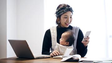 En smilende japansk kvinne holder babyen sin i en bæresele mens hun sjekker telefonen og arbeider fra en bærbar datamaskin