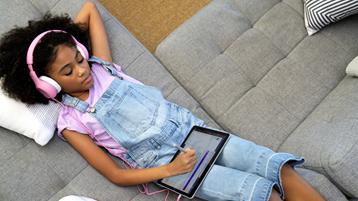 Ung svart kvinnelig student legger seg på en sofa mens hun arbeider på et nettbrett og bruker hodetelefoner