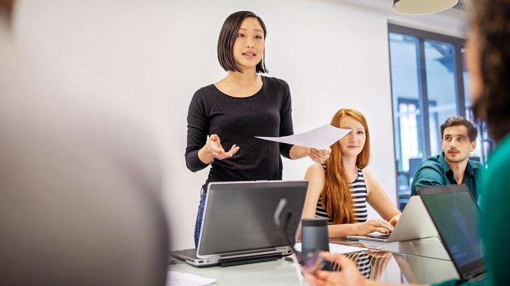 Foto van een docent die een klas een presentatie laat zien