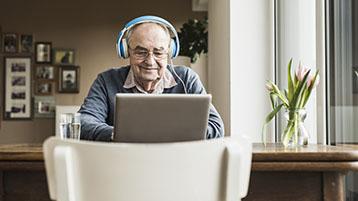 Een oudere man die een hoofdtelefoon draagt en een computer gebruikt