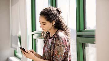 Een vrouw die bij het raam staat en die werkt op een telefoon