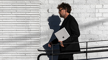 Een man die wandelt en een Surface Book vasthoudt